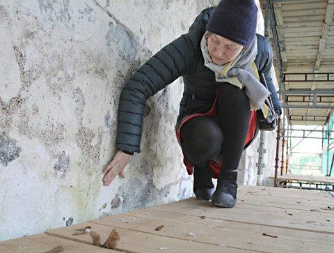 Nordveggen: Marit Linberg finner tegn på fukt under gammel mørtel. Nå skal det utbedres mot fukt på Tingvoll kirke.