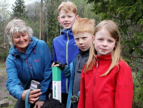 TURGLADE: Karin Østby tok med seg barnebarna Mads (10, Jørgen (8) og Vilde (7) Østby Hübert på stolpejakt i fjor. Registreringen gjøres ved å scanne en QR-kode på stolen med smarttelefonen, slik opprettholdes også smitteverntiltakene.