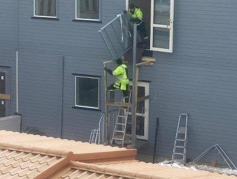 UNN ÅSGÅRD: De to bygningsarbeiderne var midt i en arbeidsoperasjon som involverte løft mellom to etasjer, da en tipser tok dette bildet.