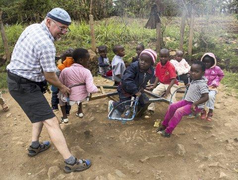 Lek i slummen: Knut Styrkson fra Ski får fart på karusellen utenfor kirken i Kawangwareslummen i Nairobi.