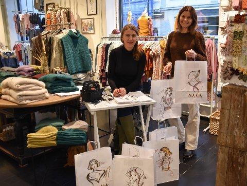 KUNSTPOSER: – Jeg tenkte at Verena Waddell er så sporty. Jeg spør om hun vil være med på dette, sier Kirsti Kvien hos Noa Noa (til høyre). Fredag satt kunstneren i klesbutikken i Storgata 14 og tegnet unike kunstposer til kundene. – Jeg bruker en begrenset palett med harmoniske fargesammensetninger, som passer til butikken, sier kunstneren. FOTO: Vibeke Bjerkaas
