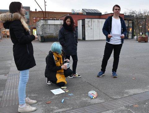 PLANLEGGER NESTE STREK: Fra venstre står Victoria Stefanov, Daiana Shin og Viljam Steinset-Strøm. På kne står Nora Pamela Skalleberg. Det vil ta litt tid å overføre skissen på arket til et bilde på asfalten på Torget. FOTO: Vibeke Bjerkaas