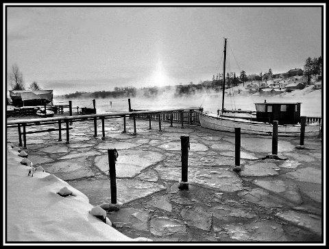 1977: En kald og guffen vintermorgen, med lav vintersol i øst. Stedet er småbåthavna på Hannestad. Isen har lagt seg , og en enslig fiskeskøyte ligger på vannet. Resten av trebåtene, på den tiden var det flest av de , er nok på land i vinterhalvåret. Isen har nok ikke lagt seg i selve elveløpet dette året. Det gjorde den derimot i årene 1942-43 under krigen. Har opp gjennom årene sett mange foto av båter fastfrosset i isen. Og folk gikk over på østsiden av elva, i tilrettelagte gangstier. En kunne rett og slett gå fra Sarpsborg til Fredrikstad (andre byen ), på isen. Hva nå enn det skulle være godt for..... Ellers ligger nå Vesten der , på østsiden av elva, litt pussig navn. Men, men; Glomma renner nå der i alle fall.