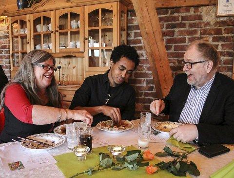 God kontakt: Kristine Fluge, Rodes Yemane AB og Haakon Aase eit mat frå Eritrea. Kristine og Haakon har vore flyktningafadder for Rodes sidan han kom til Meland i sommar. FOTO: IRENE JENSSEN