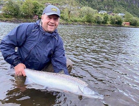 GLAD FISKAR: Jan Erik Aase med laksen på 10,2 kilo, fanga med fluge på den rolege strekninga nedanfor Naustdalsfossen.  Det store byggefeltet på sørsida av elva bak Aase.