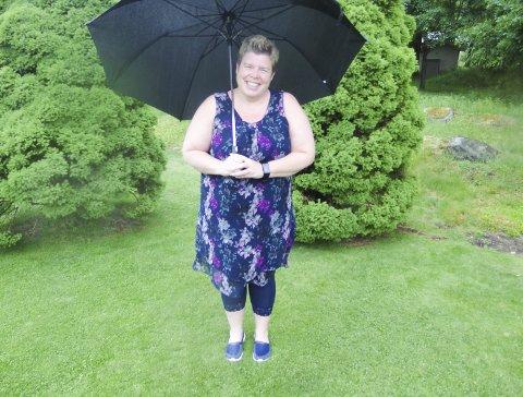SMILER: Marit Westby smiler under paraplyen. Tunge skyer er langt fra nok til å ta det gode humøret fra 50-åringen. Her står hun i hagen der det sikkert også var et humørfylt bursdagslag på lørdag.