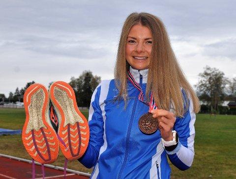 SÅNN SER DEN UT: En stolt Maren Lie med løpsskoene og bronsemedaljen hun så sensasjonelt løp inn til under NM i halvmaraton lørdag. Foto: Øivind Eriksen