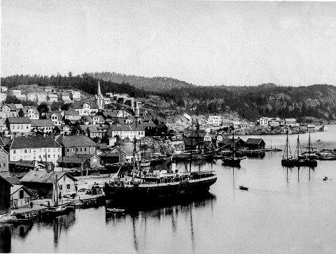 Dampskipsbrygga i Kragerø: Det er vanskelig å se når dette fotografiet ble tatt. Det må være etter bybrannen i 1886. Det ser ut som om det har kommet opp nye boliger på Stilnestangen. Siden dette var før jernbanen kom, var Kragerøs ansikt mot sjøen helt annerledes enn i dag. De fleste brukte sjøveien for å komme videre. Bildet viser kystrutebåten DS «Arendal» legge til kai. Skjæret til høyre, som i dag er en del av Jernbanekaia, ble den gang kalt for «Buene». Her hadde det store Biørnefirmaet et trelastlager.
