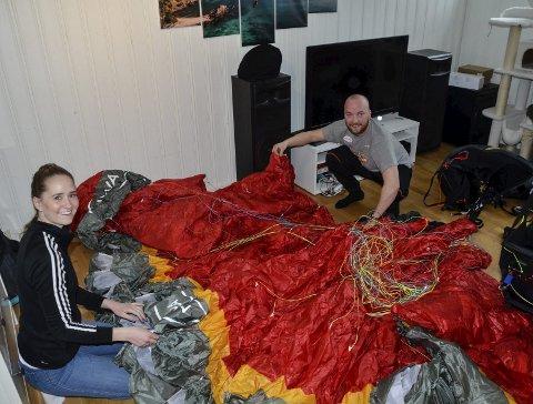 LUFTIG HOBBY: Samboerparet Sigrun Gutvik Johnsen og Jørgen Kulstad er for lengst bitt av paragliding-basillen. Her gjør de klart utstyret hjemme i kjellerstua på Båsmoen. Foto: Trond Isaksen