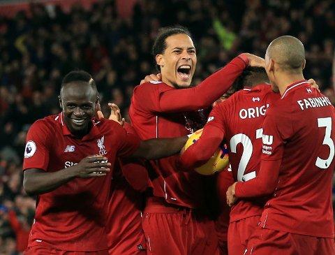 Liverpool-spissen Divock Origi jubler sammen med Virgil Van Dijik og de andre lagkameratene etter forrige sesongens 1-0-seier på Anfield. (AP Photo/Jon Super)