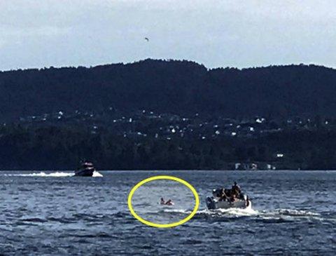Den rosa flamingoen med de to jentene oppå (innringet) får assistanse av en fritidsbåt, mens redningsskøyten kommer fossende i bakgrunnen.