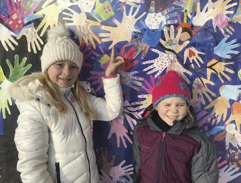 Stolte: Sanna Amalie Linna (10) og Johanne Bjerkestrand-Braathen (10) går i 5. trinn på Langeland skole og har, sammen med alle elevene ved Langeleland skole, festet hendene sine på kunstverket.bilder: erik mæhlum