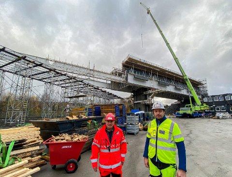 BYGGER STOR BRU: Randselva bru reiser seg bak Stig Methi (fra Statens vegvesen, til venstre) og Mariusz Urbanski (fra entreprenøren PNC). Men nå kan byggingen bli svært krevende på grunn av nye karanteneregler.