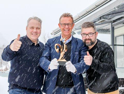 Glede: Bjørn Larsen, Håkon Johansen og Frode Gullhav er stolte som hanen, og lover en festaften du ikke vil gå glipp av. De viser fram selve prisen vinnerbedriften får. Prisen er utformet av Stig Einar Edvardsen.
