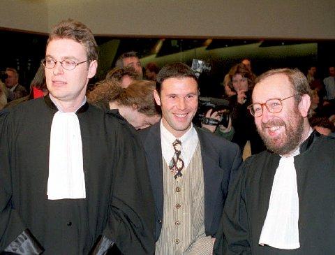 ENDRET VERDEN: Den belgiske fotballspilleren Jean-Marc Bosman endret fotballverden for alltid i 1995. Lite visste han om det store personlige offeret han ville gjøre som følge av dommen. Her et bilde fra rettsaken etter dommen falt. Til venstre er Bosmans advokat Jean-Louis Dupont og til høyre er Luc Misson. I midten er Bosman.