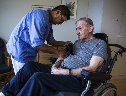 PÅ JOBB: Parabaran Rajalingam har en mastergrad i eldreomsorg, og kunne fort blitt bundet fast i møtevirksomhet. Likevel insisterer han på å ha daglig kontakt med beboerne på sykehjemmet. Her måler han blodtrykket på Arne Olsen.