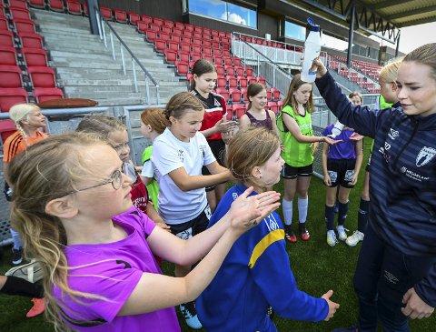 Instruktør Alva Øverås Dahlberg sørger for at jentegruppa følger koronavettreglene. Her sprites hendene til deltakerne i en pause på på fotballskolen. Foto: ØYvind Bratt