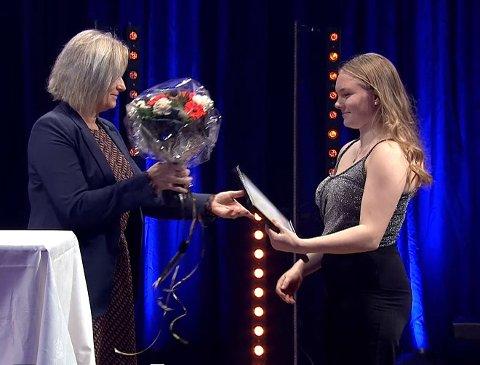UTDELING: Her får Emmeli Brodersen Ertzaas (t.h) diplom og blomster fra Fylkeskommunen ved May Britt Lagesen