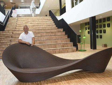 Spesiell Design: Dirk Kriedemann fra PM Danielsen Kontorutstyr trekker fram denne bølgeformede sofaen som har fått en sentral plass i bygget. Her kan elevene slenge seg nedpå på vei opp eller ned trappene. Foto: Øystein K. Darbo