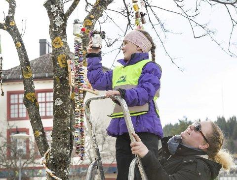 Høyt oppe: – Her skal denne henge!, Heddie Noer-Johansen har funnet en kvist høyt oppe i et av trærne i Bankparken. Helene Noer-Johansen sikrer at hun ikke faller ned når hun er så høyt på gardintrappen. BILDER: JENS HAUGEN