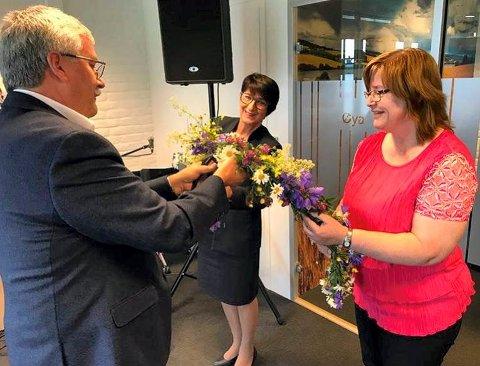 Administrerende direktør Richard Heiberg klipper blomsterkransen (i stedet for snor) mens ansatte i banken holder krans. T.v Torunn Lothe Larsen og t.h May Utstøl.  Foto: Gry Hege Haug
