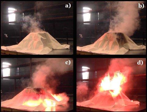 Røyksøylen over brannteppet antennes av flammer som kommer fra under teppet.
