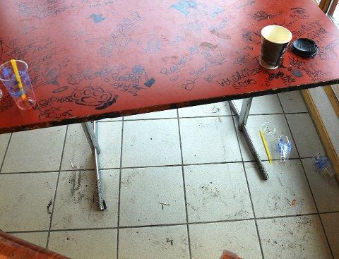 GRISET TIL: Brennmerker og tusjing på bordet, søppel og sigarettsneiper på golvet, Gran Taxi er lei tilgrising av venterommet for buss og drosje.