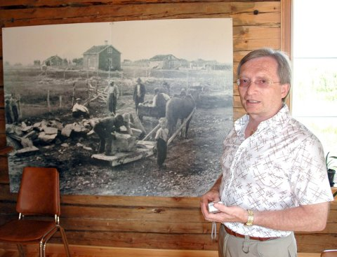 GRATULERER: Terje Aronsen fra Børselv har siden 1970-tallet jobbet iherdig med å synliggjøre, bevare og utvikle kvensk kultur, språk og historie. Bildet er fra 2004. Aronsen fortalte da blant annet om byggeskikkene i Børselv. På bildet som er bak ham, er blant annet hans far og bestefar.