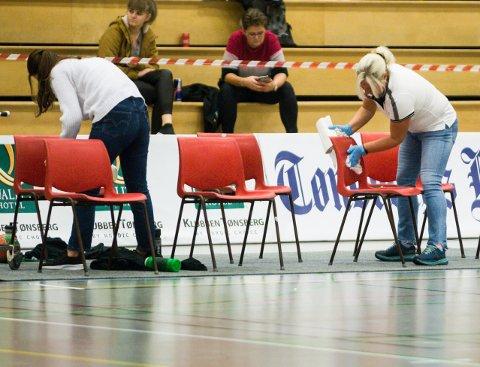 SMITTEVERN: Nøtterøy Håndball har fulgt smittevernreglene nøye ved hjemmekampene i 1 divisjon. Ikke siden august har det vært påvist smitte i spillertroppen. Her desinfiserer to frivillige innbytterstolene i pausen under en seriekamp.