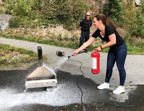 SLUKKING AV ÅPEN ILD: Elisabeth Aasbakken slukker elegant flammene med et skumapparat. Erlend Bringsli fra Nord-Aurdal brannvesen følger med på at jobben blir utført riktig