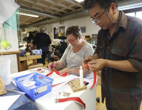 Saks og stearinlys: Berit Larsen hos Embla måler og klipper til silkebånd i rødt, hvitt og blått, mens Ngew Zaw Zaw sveiser endene på sløyfene med varmen fra et stearinlys.foto: Stig Sandmo