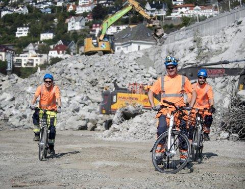 De siste ukene har syklister iført anleggsklær frekventert på gang- og sykkelveien langs Store Lungegårdsvann, samt inne på anleggsområdet, som her. Fra venstre: Mattias Rød, Espen Steend og Ole Jakob Oanes i Skanska synes el-syklene er effektive fremkomstmidler.