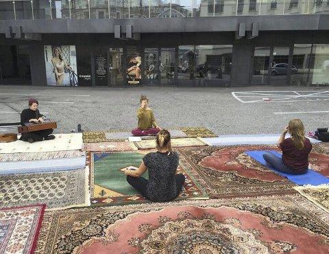 PARKERINGSYOGA: To hadde møtt frem til den første yogatimen på parkeringsplassen lørdag. Maria Sørlie Berntsen var instruktør, mens Hanna von Bergen sørget for det musikalske. Foto: Marianne Holøien