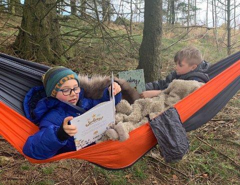 UTESKOLE: Arvid (8) (t.v.) tar leseleksen ute i naturen. Lillebror Elvin (6) øver seg til han skal starte på skolen til høsten.