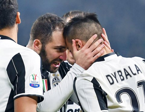 Juventus' Gonzalo Higuain, left, celebrates with teammate Paulo Dybala during the Italian Cup first leg semifinal soccer match between Juventus and Napoli, at the Juventus Stadium in Turin, Italy, Tuesday, Feb. 28, 2017. Higuain scored one goal and Dybala added two more in Juventus 3 - 1 victory. (Andrea Di Marco/ANSA via AP)