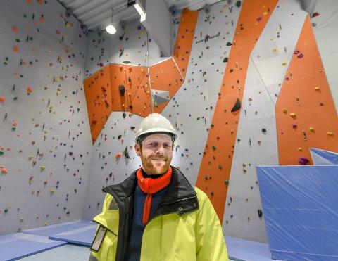 KLATREVEGG: Byggeleder Trond Meistad ved Hugaas Entreprenør, som står for byggingen av den nye flerbrukshallen på Mjølan, foran den fargerike og ni meter høye klatreveggen.