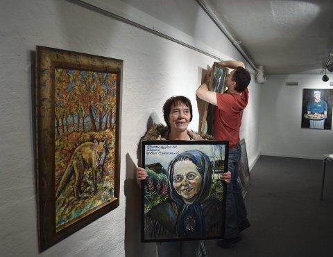 UTSTILLING: Karin Kolstad viser fram flere av sine nye og gamle bilder på Kinogalleriet. Før lørdagens åpning får hun hjelp av sønnen Jonny med å henge opp bildene. Bildet «Reven» til venstre.