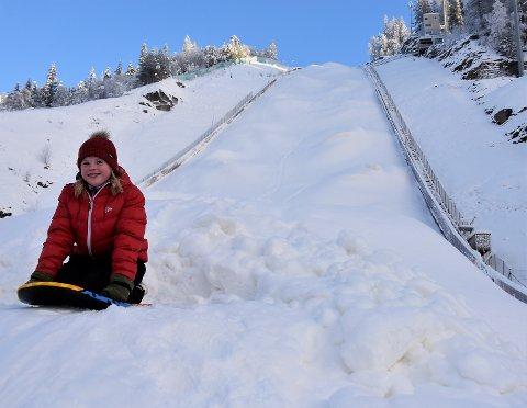 MEKTIG KULISSE: Andrea Mariboe (12) klar til en ny aketur, i bunnen av verdens største skiflygingsbakke.