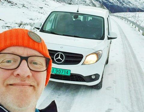 Her er Signor og bilen med piggfrie dekk. I bunnen av bakkene ligger Rekvik på Kvaløya. Foto: Privat