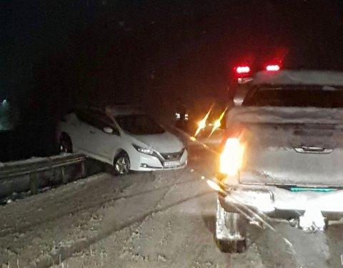 OPPÅ AUTOVERNET: Den hvite bilen skulle kjøre forsiktig forbi en lastebil med blinkende lys, men kom for langt ut i grøfta og sklei bortover autovernet.