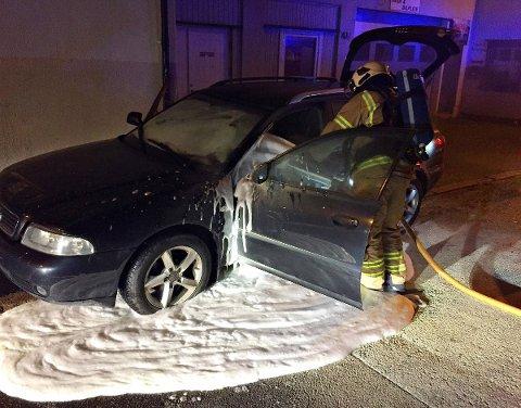 Brannmannskaper etterslukker bilbrannen som ble slukket av en beboer like ved gata.