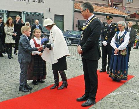 Leon Torptangen og Julie Fredèn Westby hilser på Dronning Sonja og gir henne blomsterbuketten.