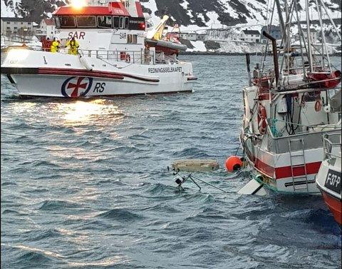 I AKSJON: Det tok redningsskøyta og brannvesenet i Kjøllefjord tre timer å få båten opp på land. På bildet kan man såvidt skimte toppen av båten i vannflata. Hele båten gikk nemlig under i stormen.