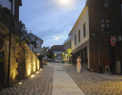I kveldslyset: Torsdag kveld ble den nye gatebelysningen tent i Hovedgata. Tvers overfor Tvedestrandsposten er det lagt ned i gata noen lyspunkter som lyser opp den fine stein-muren. Ellers er det flere andre spesielle lyspunkter nedover gata, som trer godt fram i kveldsmørket. Foto: Øystein K. Darbo