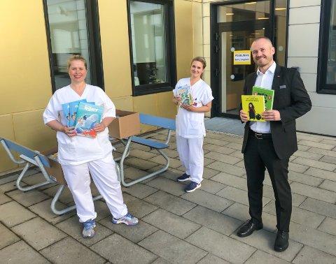 BOKGAVE: Susan Christianslund (til venstre) og Kristine Solvang tok i mot bøker av hotelldirektør Kjetil Fløyli utenfor sykehusets barneavdeling. Nå får de yngste 55 nye bøker å titte i.