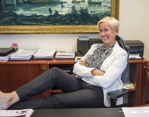 Gina Merethe Johnsen tror ikke det blir mange muligheter for å legge beina på bordet, men gjør det til ære for fotografen. Involvering, samarbeid og mer til de eldre er stikkord for Frps ordførerkandidat. Foto: Nils-Erik Kvamme