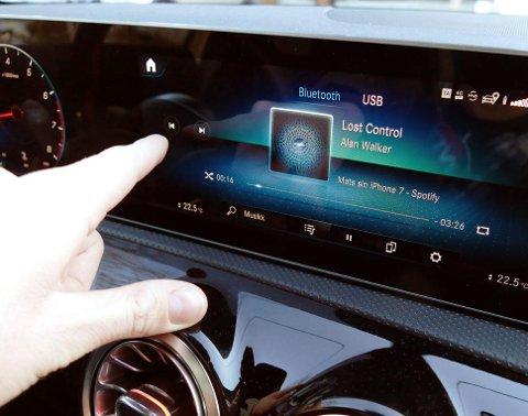Lovlig: Å bytte sang på bilens infotainmentskjerm er ikke straffbart. Her flytter man også blikket fra veien