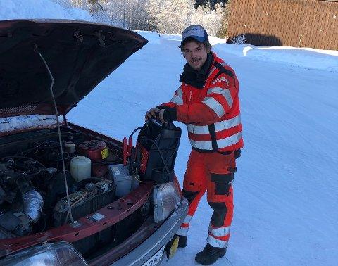 PÅ OPPDRAG: Daniel Henriksen hos Bilberging Valdres AS i gang med å få fart i et slitent batteri. Foto: Bilberging Valdres AS