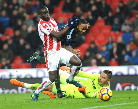 Manchester City's Raheem Sterling, centre, is tackled by Stoke's Badou Ndiaye during the English Premier League soccer match between Stoke City and Manchester City at the Bet 365 Stadium in Stoke on Trent, England, Monday, March 12, 2018. (AP Photo/Rui Vieira)