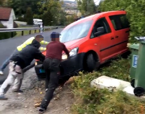 DRAMATISK: Her forsøker flere personer å få bilen ut av hekken etter at den førerløse bilen trillet 50-70 meter ned en bakke. Foto: RB-TIPSER